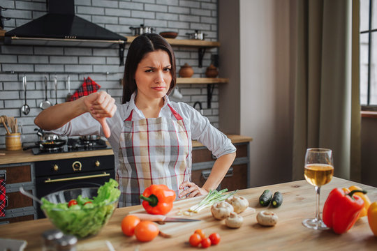 Young unhappy woman sit at table in kitchen. She look on camera and hold big thumb down. Woman upset. Vegetables on table. Glass on wine on desk.