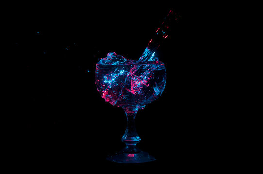 Water overflowing into cup under colorful lights on a black background