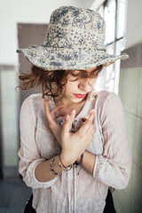 Beautiful ethnic hippie female keeping hands near chest and closing eyes while standing inside apartment building after party