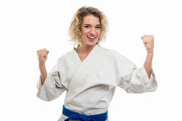 Portrait of female wearing martial arts uniform making winner gesture