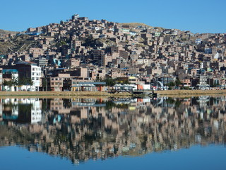 the town of Puno reflected on Titicaca lake, Peru
