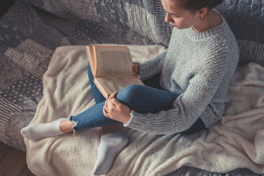 Cold autumn or winter weekend while reading a book and drinking Lazy day with cat on the sofa. Cosy scene, hygge concept