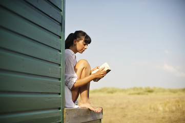 Side view of young woman reading book outdoors