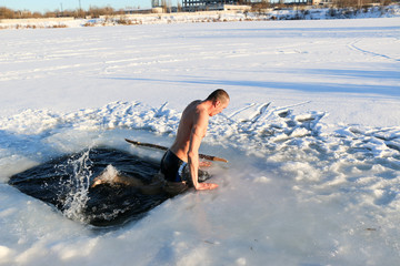 Young man standing by ice hole and ready to swim in the winter water