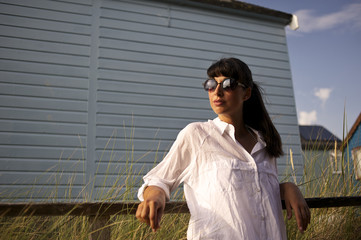 Young woman wearing sunglasses standing near beach hut
