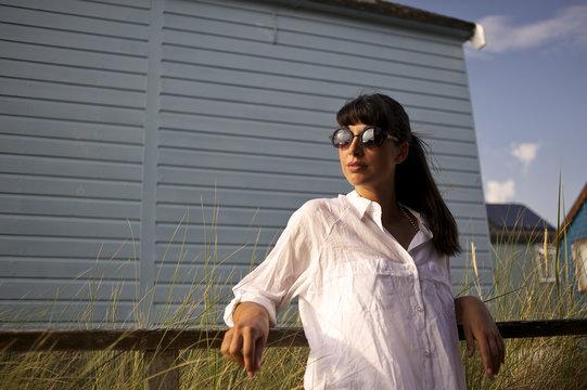 Young woman wearing sunglasses standing near beach hut