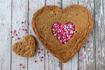Huge Heart-shaped chocolate chip cookie with heart cutout in center filled with candy hearts