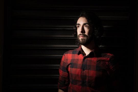 LGBT Chilean Man with beard in plain shirt stands against dark urban backdrop