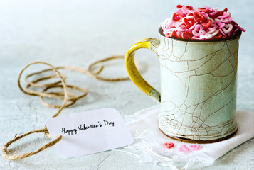 Valentine's day: sugar candies of hearts in a cup on delicate background
