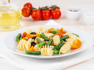 Italian salad with fusilli paste tomatoes, olives, green beans, side view, close up