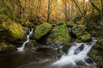 Waterfalls between granite rocks covered with moss