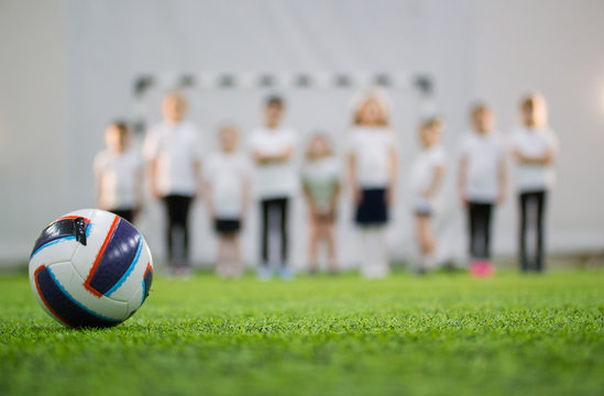 Children stand in the line on a football field. Football ball on the foreground