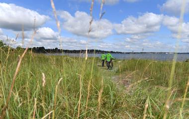 zwei Fahrradfahrer schieben ihre Fahrräder zwischen den Dünen am Strand entlang