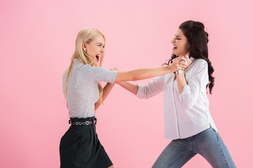 Aggressive girls screaming and fighting isolated on pink