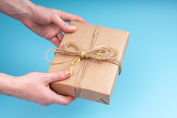 Hands holding gift box Packed in Kraft paper on blue background. Holiday card for Valentine's day and women's day