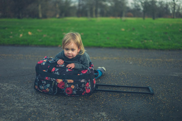 Little toddler resting on suitcase in park