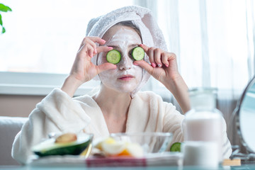 Beautiful young woman with natural cosmetic mask and cucumber slices on her face. Skin care and Spa treatments at home