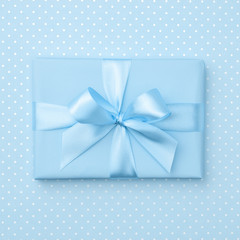Gift box with blue ribbon bow on blue speckled background top view. Holiday concept, birthday gift, 8 march or Women day, gift box presents holiday Mothers day. Greeting card with space. Flat Lay