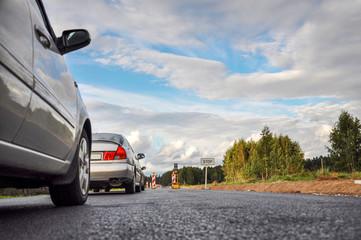A row of cars at the road repair semaphore, selective focus - image