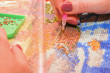 Girl collect diamond painting. Diamond embroidery with a pen. Closeup, selective focus