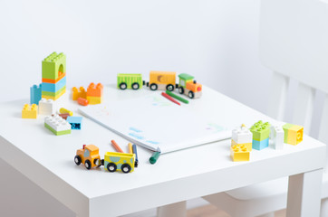 White table in the bright children's room with pencils, toy train, colorful plastic block and an album with children's drawings. Children's drawing table.