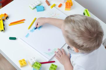 Little child draws in his album on a white table. Pencils, train, colorful plastic block in the children's room.