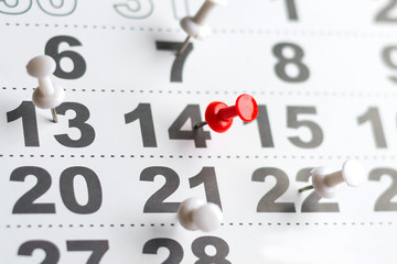 Calendar with numbers marked with white and red push pins. The number of February 14. Background for Valentine's Day.