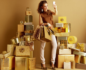 fashion-monger with shopping bags taking selfie with cellphone