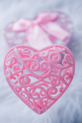 Pink lace heart. Box in the shape of a heart on a white fur rug.