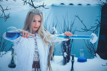 Winter Beauty Woman. Beautiful fashion model girl with glass flasks hairstyle and make-up in winter laboratory. Festive makeup and manicure. Winter Queen with snow and ice hairstyle. magic with snow
