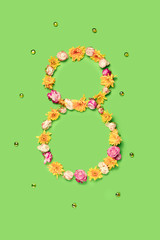The conceptual composition from flowers about Eights march woman's day, holiday on a green background. The number 8 in decor. Top view