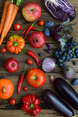 red, purple fruits and vegetables on wooden background.  Healthy food. Multicolored raw food. Copy space