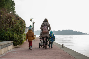 Young mother walking on a promenade along the sea pushing a stroller