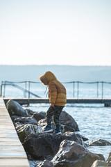 Toddler boy walking on huge rocks by the sea