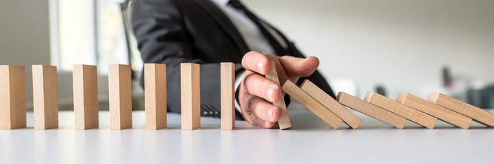 Business mediator stopping falling wooden dominos with his hand