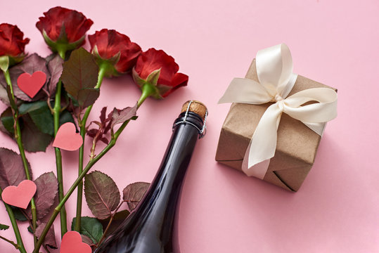 Surprise for her. Special gift box with white ribbon, red roses and champagne