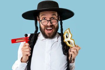 Portrait of a young orthodox Hasdim Jewish man with wooden Grager Ratchet at Jewish festival of Purim at studio. The purim, jewish, festival, holiday, celebration, judaism, pastry, tradition, cookie