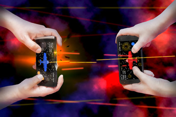 Two pairs of hands hold smartphones and enthusiastically play mobile online game. Concept - mobile multiplayer entertainment.