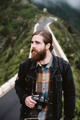 Bearded stylish guy with professional photo camera looking away while standing on asphalt road on mountain ridge