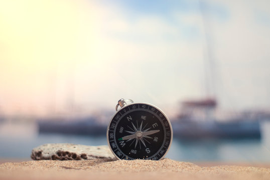 Time to travel. An idea for tourism with a compass in the sand with corals in the background of the sea and a parking for yachts.