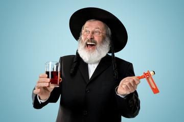 Portrait of old senior orthodox Hasdim Jewish man with wooden Grager Ratchet at Jewish festival of Purim at studio. The purim, jewish, festival, holiday, celebration, judaism, pastry, tradition