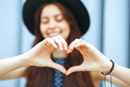 Closeup portrait of joyful brunette model in hat making heart shape with her hands
