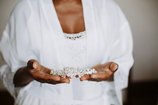 African American bride holds wedding accessory in her arms