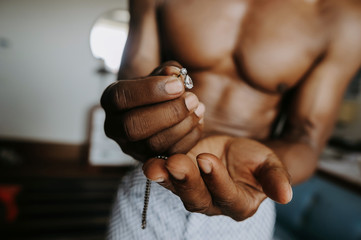 Golden chain and cufflinks lie in African American man's arms