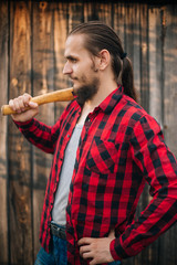 A lumberjack in red black clothes. Bearded man with an ax on a wooden background in a shirt in a cage