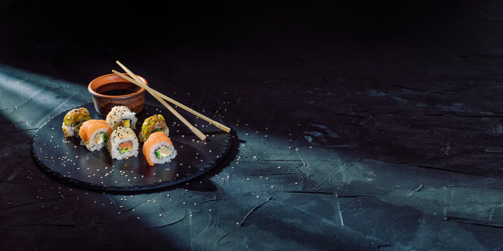 A different assortment of sushi rolls on a black coal board and a dark background. Traditional Japanese cuisine. Food with copy free space for text, logo