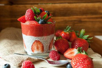 Low Carb Strawberry and chia puddings in a glass, wood background