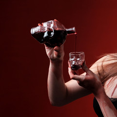Bottle and glass in the form of a skull. Female hands pour wine or blood. Red background. Halloween celebration concept. Close-up. Square picture frame.