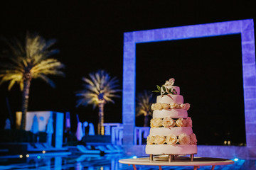 Classy white wedding cake with flowers stands on a little table outside