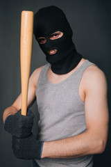 Bandit, the criminal in a black mask and in a gray T-shirt with a painless bat. Robber with a weapon. A man in a balaclava and a gray mask on a gray background
